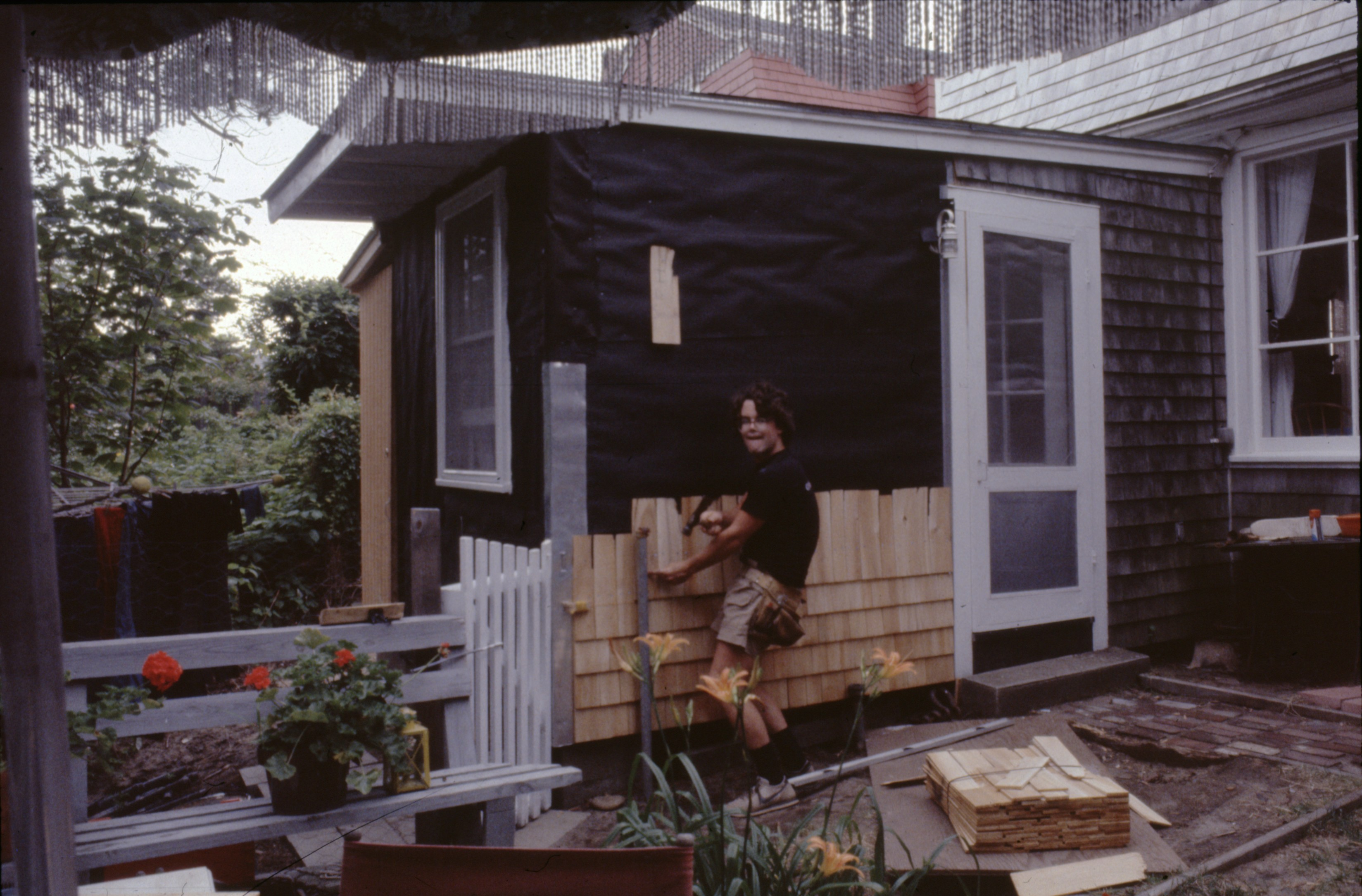 Dan Kearney installs siding on a house as a young man